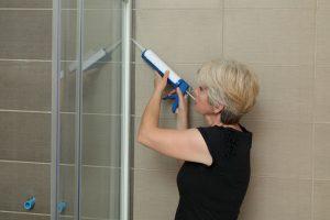 Eine Frau zeigt, wie man die Dusche richtig abdichtet