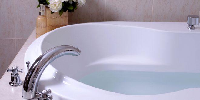 Weiße Badewanne mit silberner Amatur und Blumendeko