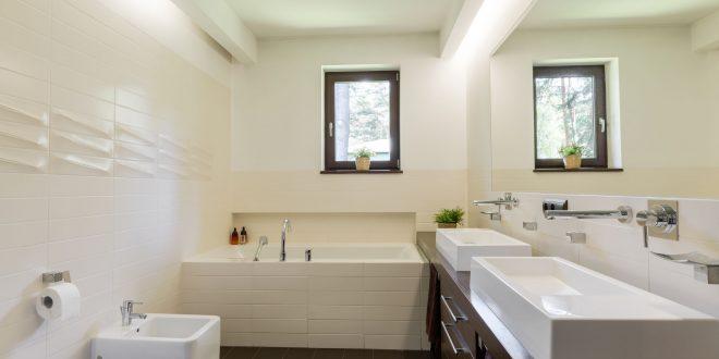 Badezimmer mit weißen Amaturen und braunem Holz