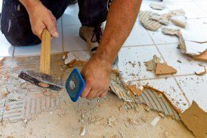 Handwerker klopft alte Fliesen vom Boden ab.