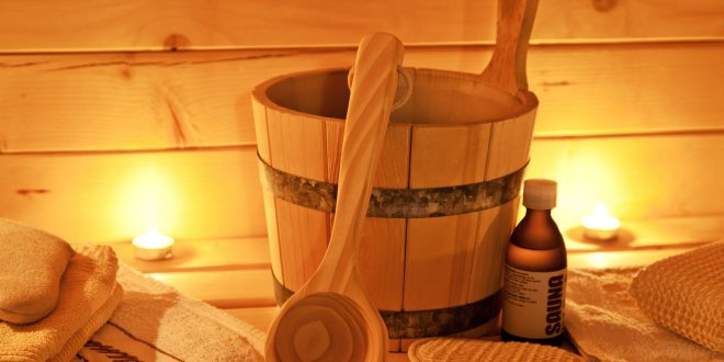 Sauna Utensilien mit Handtuch und Licht im Hintergrund