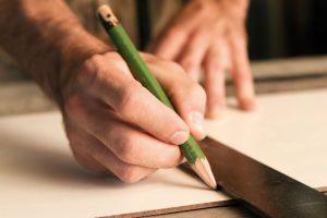 Mensch misst Holz mit Lineal und Bleistift aus