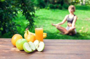 Frau macht Yoga auf einer Wiese. Obst und Getränk im Vordergrund im Vordergrung